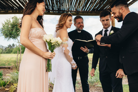 Photo pour Traditional wedding ceremony of couple outdoors. Best man giving wedding rings to groom before rings exchange ceremony. - image libre de droit