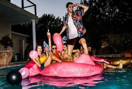 Photo for Group of friends having party in a pool in evening. Young people on air mattress in pool enjoying party. - Royalty Free Image