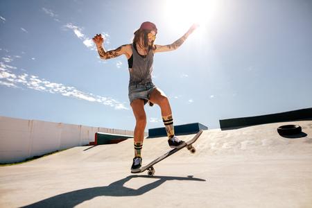 Photo pour Female skater skateboarding at skate park. Women doing tricks on skateboard. - image libre de droit