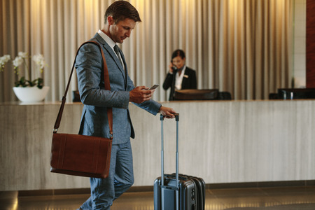 Photo pour Young businessman walking in hotel lobby and using mobile phone. Business traveler arriving at his hotel. - image libre de droit