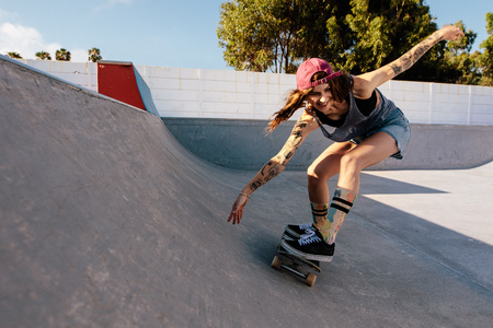 Photo pour Skater female rides on skateboard at skate park ramp. Young woman practising skateboarding outdoors at skate park. - image libre de droit