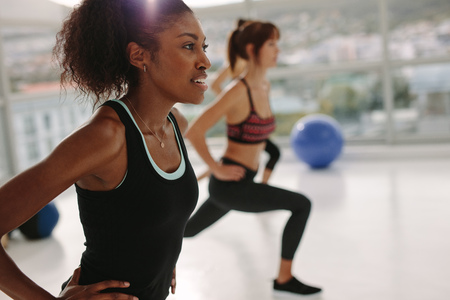 Foto de African young woman exercising in gym class. Stretching workout session in health center. - Imagen libre de derechos