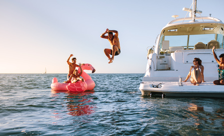 Photo pour Man diving in the sea with friends sitting on yacht and inflatable toy. Group of friends enjoying a summer day on a inflatable toy and yacht. - image libre de droit