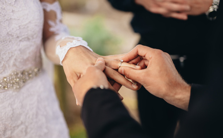 Photo pour Closeup of groom placing a wedding ring on the brides hand.  Couple exchanging wedding rings during a wedding ceremony outdoors. - image libre de droit
