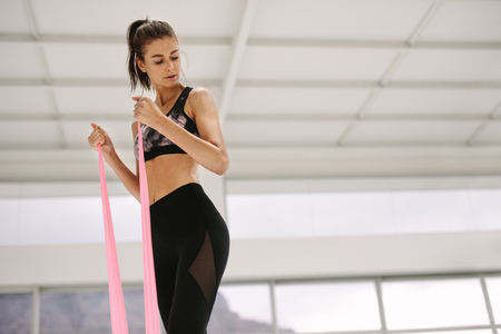 Photo pour Fit woman using resistance band for arms exercise at gym. Caucasian female working out with elastic bands at fitness studio. - image libre de droit