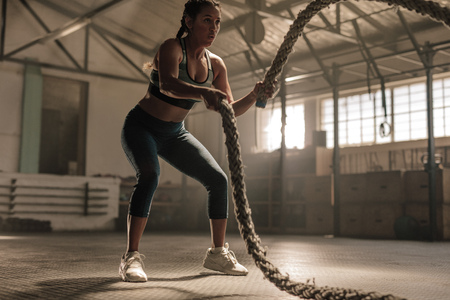 Photo for Young woman doing strength training using battle ropes at the gym. Athlete moving the ropes in wave motion as part of fat burning workout. - Royalty Free Image