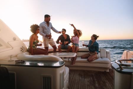 Photo pour Group of happy friends having a boat party. Diverse men and women having drinks at sunset yacht party and dancing. - image libre de droit