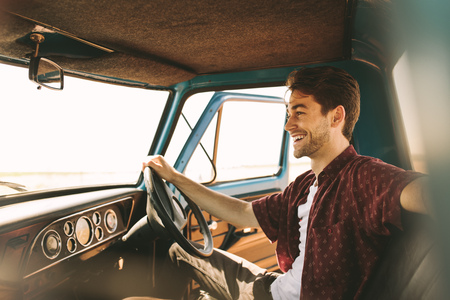 Foto de Smiling man sitting in the driver seat of an old car. Man sitting in his vintage car holding the steering wheel with the door open. - Imagen libre de derechos