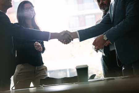 Photo for Successful business associates shaking hands after a deal. Business people hand shake and greeting each other after an agreement during meeting. - Royalty Free Image