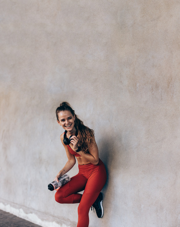 Photo for Smiling young woman sportswear standing by a grey wall. Female athlete with water bottle taking break after training session outdoors. - Royalty Free Image