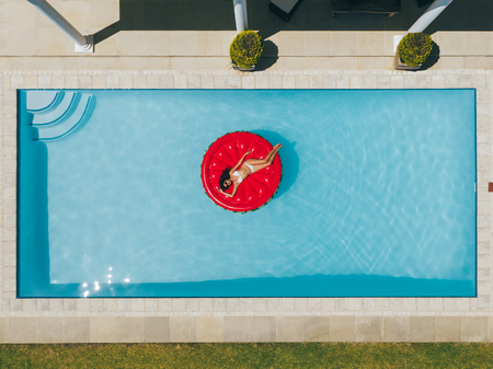 Photo pour Aerial view of woman relaxing on a inflatable mattress in resort pool. Top view of female in bikini floating on inflatable mattress in pool. - image libre de droit