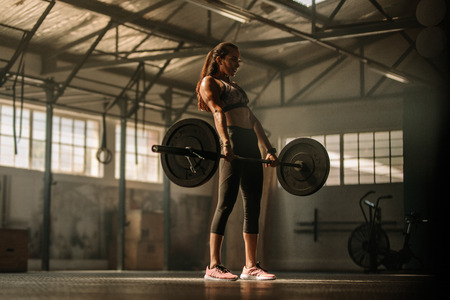 Photo pour Strong female athlete holding a barbell in her hands. Cross fit woman lifting heavy weights in gym. - image libre de droit