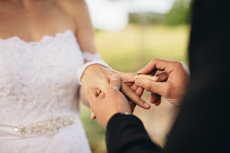 Photo pour Closeup of couple exchanging wedding rings during their wedding ceremony outdoors. Cropped shot of groom putting a wedding ring on the finger of the bride. - image libre de droit