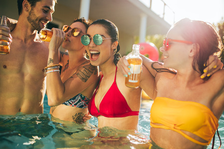 Photo pour Multiracial group of friends having fun in a pool party. Group of men and women drinking and enjoying together in the swimming pool. - image libre de droit