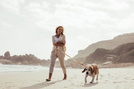 Photo pour Full length shot of mature woman taking her dog on walk on the beach. Senior female on morning walk with her pet dog. - image libre de droit
