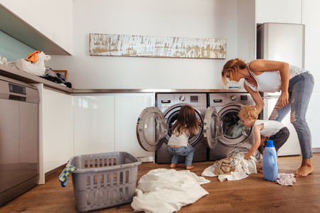 Foto de Woman with kids load clothes in washing machine. Mother and children putting laundry into washing machine at home. - Imagen libre de derechos