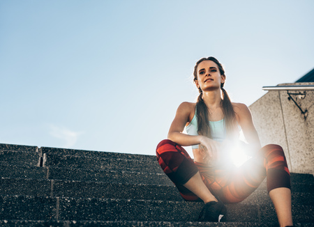 Photo pour Health young woman sitting on stairs outdoors in morning. Female athlete taking rest after workout with sun flare. - image libre de droit