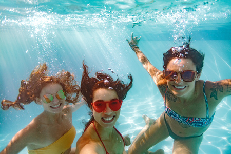Photo pour Happy young women friends swimming underwater in pool. Underwater shot of smiling females in pool taking selfie. - image libre de droit