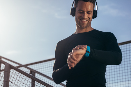 Foto per Man standing outdoors with headphones using a smartwatch to monitor his progress. Male athlete resting and checking his performance on fitness smartwatch device. - Immagine Royalty Free