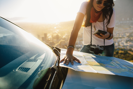Photo pour Young solo traveler looking at mobile phone and tourist map on car hood. Young female tourist on a road trip searching for directions. - image libre de droit
