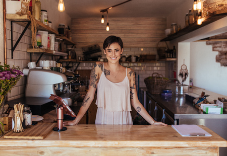 Photo pour Woman standing at the billing counter of her cafe posing. Smiling restaurant owner standing beside the billing machine. - image libre de droit