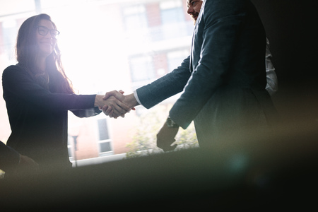 Photo for Businesswoman shaking hands with businessman after a successful agreement in office meeting. Businesspeople hand shake after a deal. - Royalty Free Image