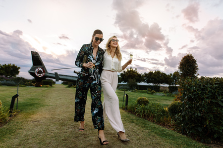 Foto de Full length of two young women walking together with a helicopter parked in background. Stylish females enjoying a luxurious lifestyle. - Imagen libre de derechos