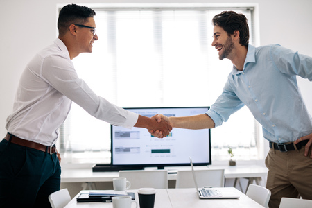 Photo for Business colleagues shaking hands in the conference table. Happy businessmen greeting each other in the meeting room. - Royalty Free Image