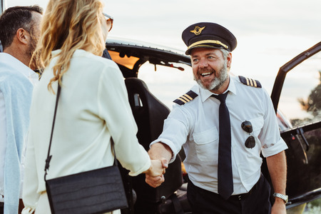 Foto de Helicopter pilot shaking hands with woman and smiling. Couple traveling through a private helicopter with pilot greeting them. - Imagen libre de derechos