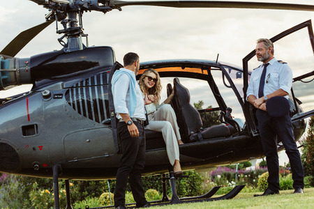 Photo pour Beautiful woman getting down the helicopter with the help from her boyfriend. Couple disembarking their helicopter with pilot standing by. - image libre de droit