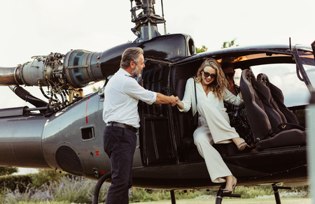 Foto de Pilot holding hand of a woman getting off the helicopter. Wealthy young woman traveling by her helicopter. - Imagen libre de derechos