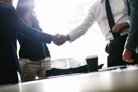 Photo for Partners concluding deal and shaking hands in the presence of team members. Businessmen shaking hands in board room and finishing up a meeting. - Royalty Free Image