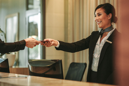 Photo for Smiling receptionist behind the hotel counter attending female guest. Concierge giving the documents to hotel guest. - Royalty Free Image
