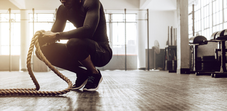 Photo pour Man sitting on his toes holding a pair of battle ropes for workout. Crossfit guy at the gym working out with fitness rope. - image libre de droit