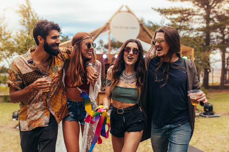 Foto de Group of men and women at music festival having beers and enjoying. Friends having a great time at music festival in a park. - Imagen libre de derechos