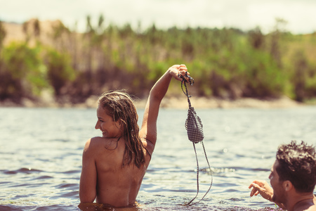 Foto de Woman in the lake holding her bikini top and smiling with boyfriend. Loving couple enjoying their summer vacation in a lake. - Imagen libre de derechos