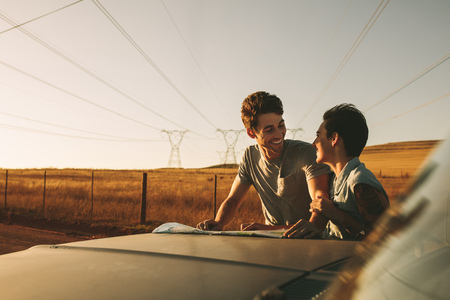 Foto de Couple looking at a map for navigation while on a road trip. Man and woman using a map to navigate through the country side. - Imagen libre de derechos