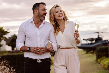Photo pour Handsome man with his beautiful girlfriend walking together outdoors. Beautiful couple walking outdoors with a helicopter at the back. - image libre de droit