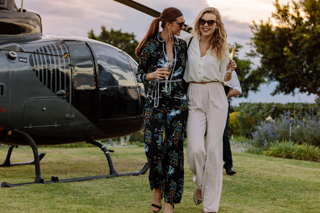Foto de Two young women walking away from a helicopter with a glass of wine in their hands. Best friends walking together with wine and having fun. - Imagen libre de derechos
