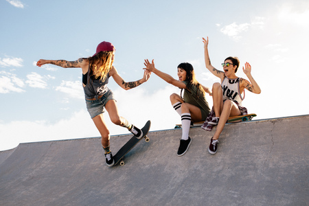 Photo pour Female skateboarder riding skateboard at skate park with friends sitting on ramp having fun. Woman skater giving high five to female friend sitting on ramp during her routine. - image libre de droit