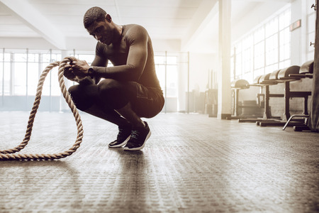 Photo for Man sitting on his toes holding a pair of battle ropes for workout. Crossfit guy at the gym working out with fitness rope. - Royalty Free Image