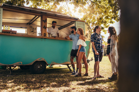 Foto de Young people buying street food from a food truck at park. Group of men and woman at food truck. - Imagen libre de derechos