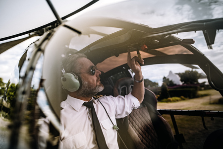 Photo pour Pilot with headset starting the controls in the private helicopter. Helicopter pilot sitting in the cockpit. - image libre de droit