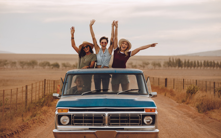 Foto de Group of female friends riding in pickup truck having fun on summer day. Three women standing at the back of pickup truck with their arms raises and smiling. - Imagen libre de derechos