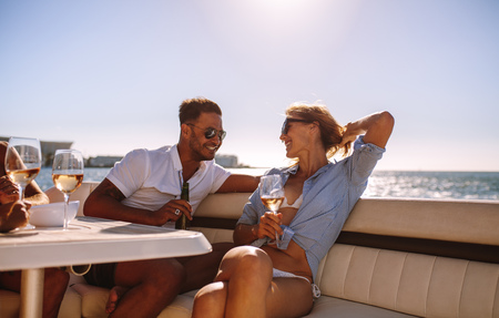 Photo pour Smiling couple sitting on a boat with drinks. Relaxed young people during a boat party. - image libre de droit