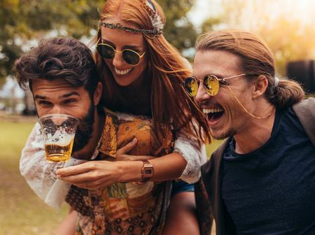 Foto de Cheerful young people having fun outdoors at park. Men and woman piggybacking and having beer. - Imagen libre de derechos