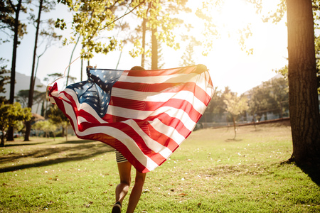 Photo for Woman running with american flag on a sunny day. Shot from behind of a girl running in the park with American flag. - Royalty Free Image