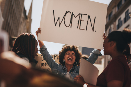 Photo pour African woman holding a banner and laughing during women march. Group of female demonstrating outdoors with placards. - image libre de droit