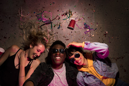 Foto de Top view of man and two women lying on floor and laughing at a house party. Friends lying on floor at the house party with cups and confetti around. - Imagen libre de derechos