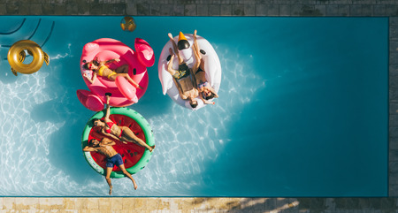 Photo for Aerial view of young people on summer vacation enjoying on fun inflatable floats in swimming pool. Group of friends relaxing on air mattresses in pool. - Royalty Free Image